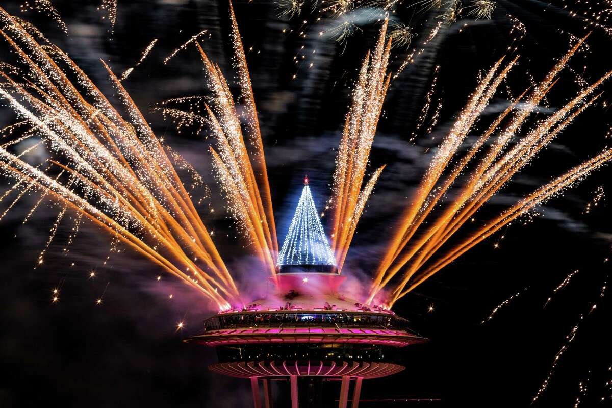 Colorful bursts of fireworks explode along the 605-foot height of the Space Needle during the