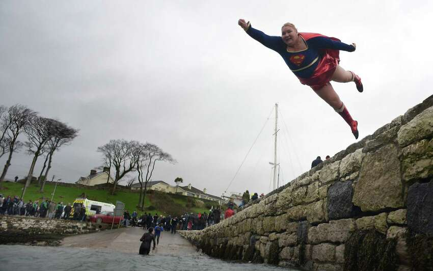 You don't have to be Superman or Superwoman to do this. But it helps. Angela McClements takes the plunge as swimmers brave the icy waters during the New Year's Day swim at Carnlough harbour on Jan. 1, 2015, in Carnlough, Northern Ireland. The annual event on the north Antrim coast upports Spina Bifida and Hydrocephalus charities.