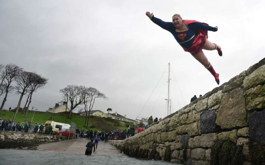 You don't have to be Superman or Superwoman to do this. But it helps. Angela McClements takes the plunge as swimmers brave the icy waters during the New Year's Day swim at Carnlough harbour on Jan. 1, 2015, in Carnlough, Northern Ireland. The annual event on the north Antrim coast upports Spina Bifida and Hydrocephalus charities. Photo: Charles McQuillan, Getty / 2015 Charles McQuillan