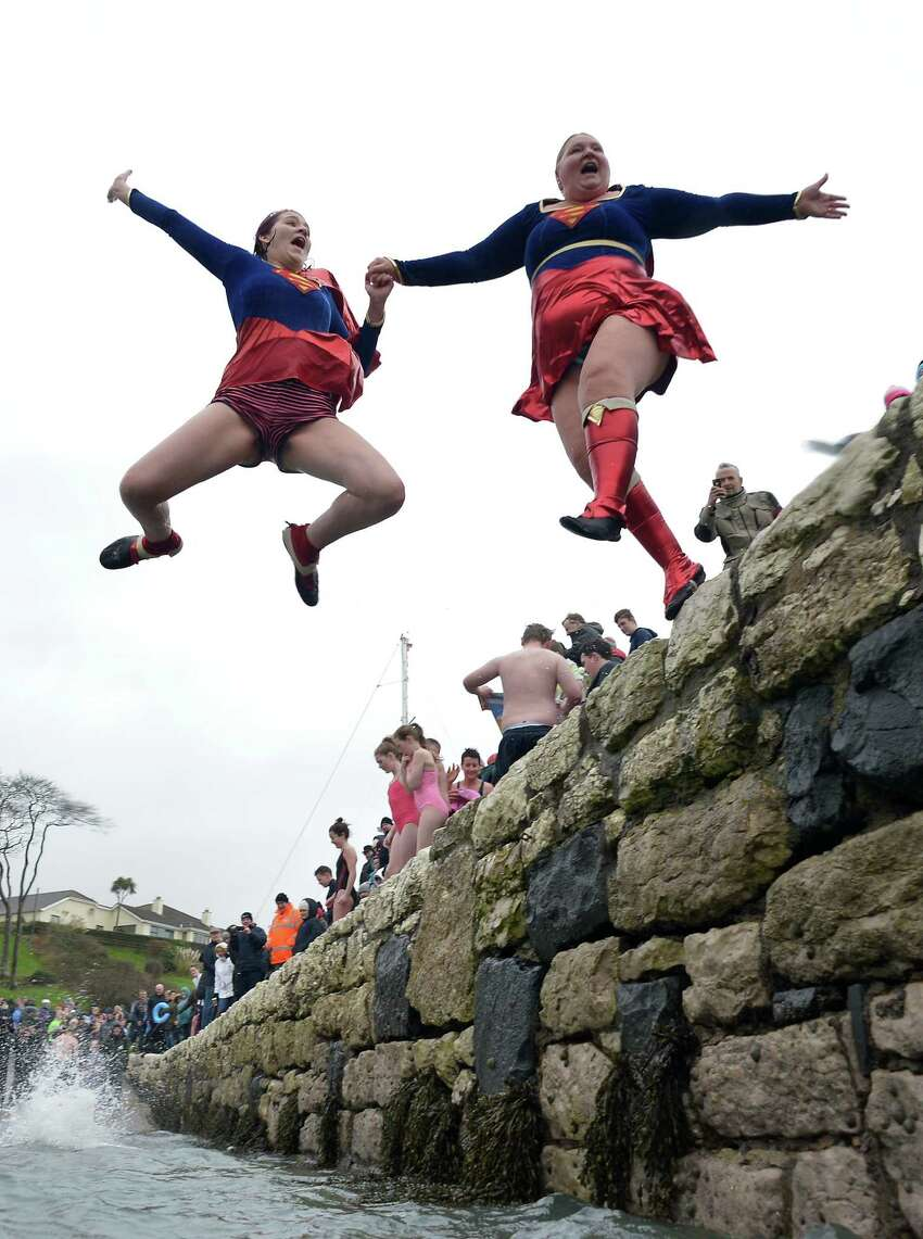 More super heroes take the plunge during the New Year's Day swim at Carnlough harbour in Carnlough, Northern Ireland.