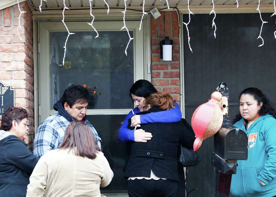 A family friend holds onto the daughter of Javier Suarez Rivera, Keyla Rivera, 16, as family and friends grieved outside the home where Javier was struck and killed by a stray bullet around 1 a.m. Photo: Johnny Hanson/Family Photo
