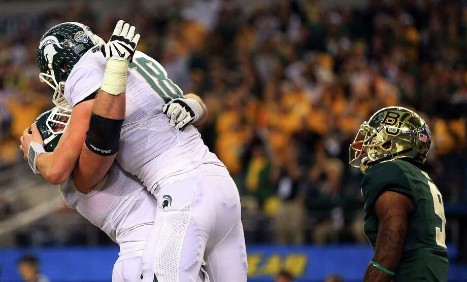 Connor Cook (right) of the Michigan State Spartans and Brian Allen celebrate after a game-winning touchdown pass in the final seconds against the Baylor Bears. Photo: Ronald Martinez /Getty Images / 2015 Getty Images