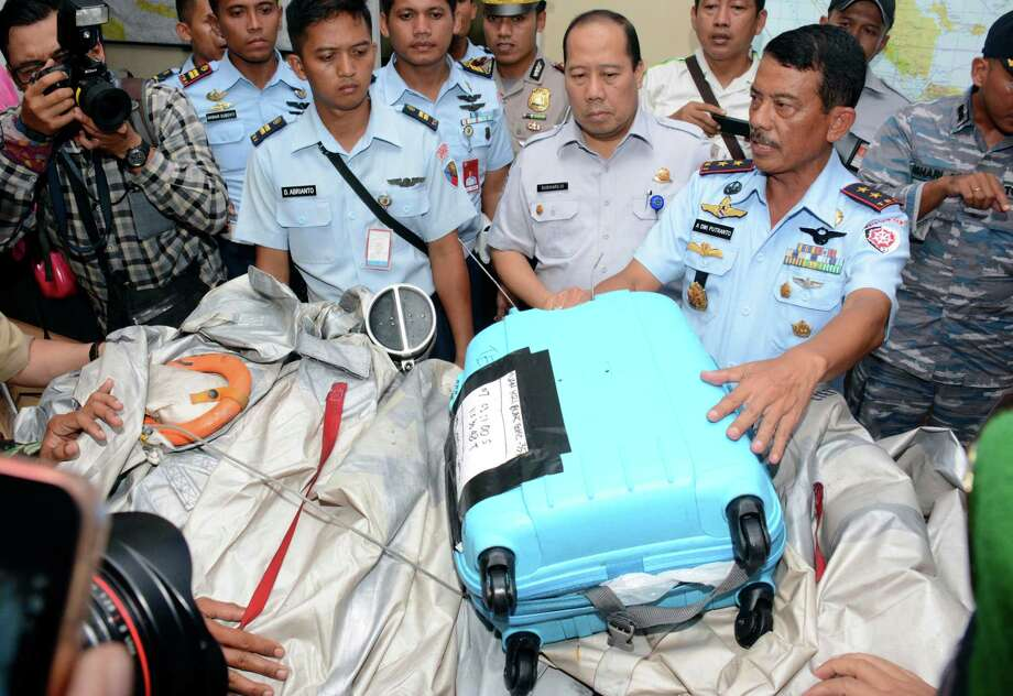 """Commander of 1st Indonesian Air Force Operational Command Rear Marshall Dwi Putranto, right, shows airplane parts and a suitcase found floating on the water near the site where AirAsia Flight 8501 disappeared, during a press conference at the airbase in Pangkalan Bun, Central Borneo, Indonesia, Tuesday, Dec. 30, 2014. Bodies and debris seen floating in Indonesian waters Tuesday, painfully ended the mystery of AirAsia Flight 8501, which crashed into the Java Sea and was lost to searchers for more than two days. The writings on the suitcase reads """"Recovered by KRI Bung Tomo.""""  KRI Bung Tomo is the name of an Indonesian Navy ship. The numbers on the suitcase are the coordinates. Photo: Dewi Nurcahyani, AP / AP"""