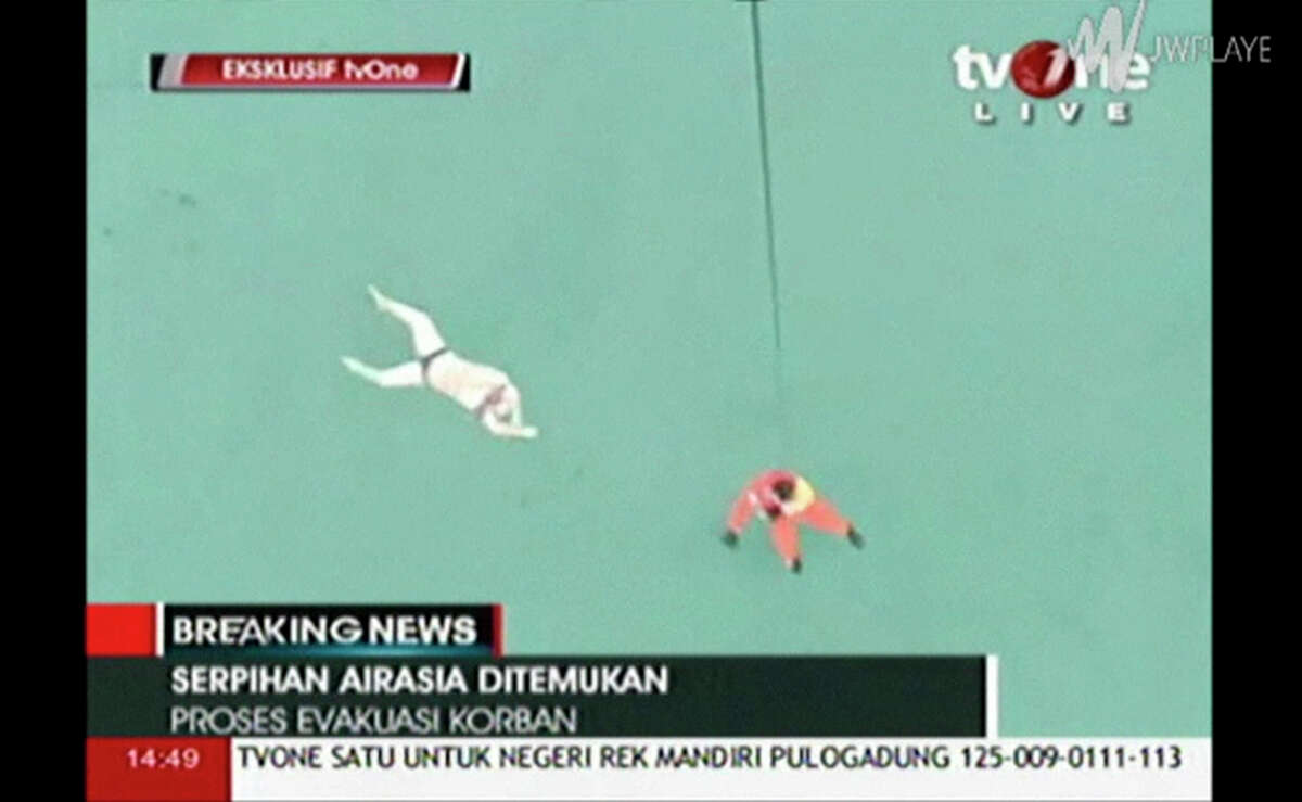 In this image taken from video released by TV One, a rescuer is lowered on rope from a hovering helicopter near a body in Java Sea waters, Indonesia Tuesday, Dec. 30, 2014. Indonesian officials on Tuesday spotted six bodies from the AirAsia flight that disappeared two days earlier, and recovered three of them, in a painful end to the aviation mystery off the coast of Borneo island.