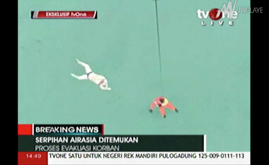 In this image taken from video released by TV One, a rescuer is lowered on rope from a hovering helicopter near a body in Java Sea waters, Indonesia Tuesday, Dec. 30, 2014.  Indonesian officials on Tuesday spotted six bodies from the AirAsia flight that disappeared two days earlier, and recovered three of them, in a painful end to the aviation mystery off the coast of Borneo island. Photo: TV One Via AP Video, AP / TV One via AP Video