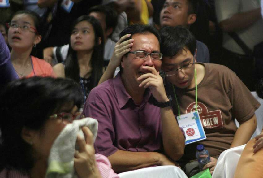 Relatives of passengers of the missing AirAsia Flight 8501 react upon seeing the news on television about the findings of bodies on the waters near the site where the jetliner disappeared, at the crisis center at Juanda International Airport in Surabaya, East Java, Indonesia, Tuesday, Dec. 30, 2014. Bodies and debris were seen floating in Indonesian waters Tuesday, painfully ended the mystery of AirAsia Flight 8501, which crashed into the Java Sea and was lost to searchers for more than two days.