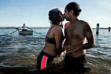 A couple share a kiss amidst the frigid waters of Pontiac Bay during the 13th Annual Polar Bear Plunge Thursday, Jan. 1, 2015, at Matthews Beach Park in Seattle, Washington. About 300 people participated in the first Polar Bear Plunge in 2003; since then, attendance has skyrocketed.