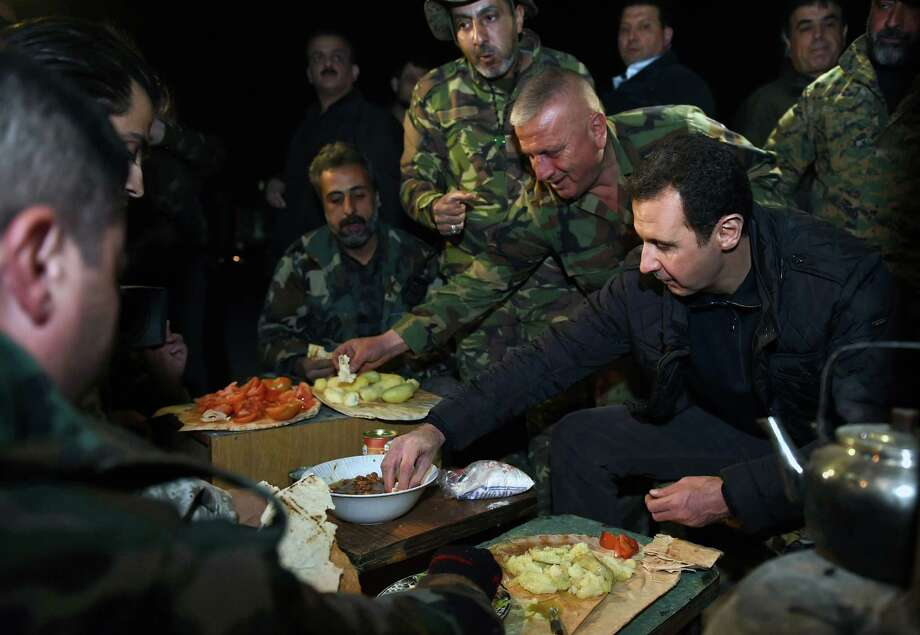 President Bashar Assad, right, minus his signature mustache, makes a morale-boosting New Year's Eve visit with his troops in eastern Damascus. Photo: Uncredited, HOPD / SANA