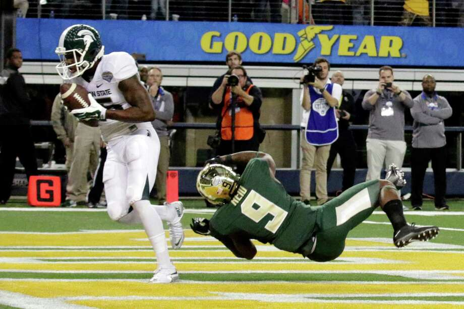 Michigan State wide receiver Keith Mumphery (25) catches a touchdown pass against Baylor cornerback Ryan Reid (9) during the fourth quarter of the Cotton Bowl NCAA college football game Thursday, Jan. 1, 2015, in Arlington, Texas.  Michigan State won 42-41. Photo: LM Otero, AP / AP