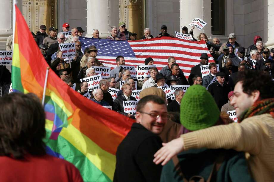 Supporters of Arkansas' law banning same sex marriage, top, hold a rally last November at the Arkansas state Capitol in Little Rock, as protesters carry flags and shout. A variety of challenges remain for gay rights advocates. Photo: Danny Johnston, STF / AP
