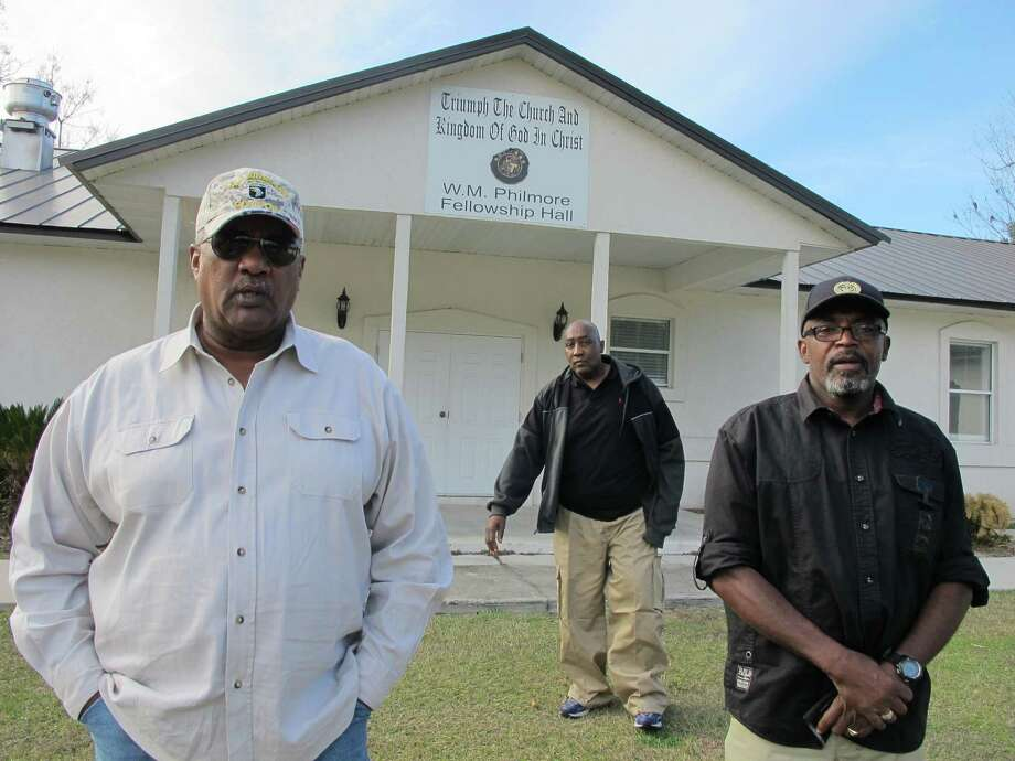 """In this Thursday, Dec. 18, 2014 photo, Alonzo Philmore, left, Harry Campbell, center, and Suwannee County NAACP president Leslie White stand in front of their church in Live Oak, Fla.  In 1952 a wealthy black woman named Ruby McCollum was found guilty by an all-male, white jury for the murder of a prominent white doctor and state senator-elect, Clifford Leroy Adams. A new documentary """"You Belong To Me"""" compiles a decade of research and first-time interviews with surviving family members on both sides, and has reopened some old wounds in the small town. (AP Photo/Jason Dearen) Photo: Jason Dearen, STF / AP"""