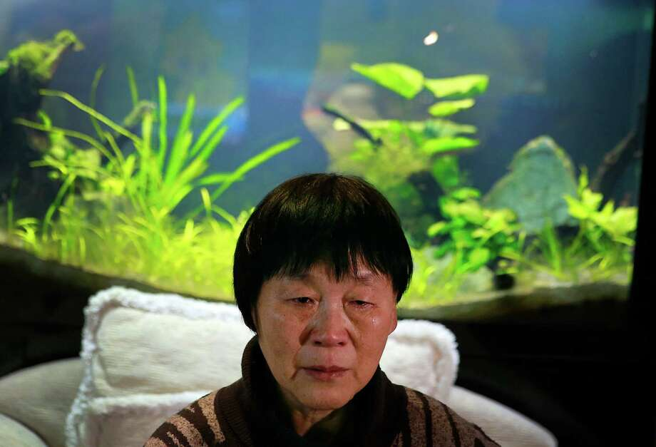 """In this Sunday, Dec. 28, 2014 photo, Dai Shuqin, whose sister was aboard Malaysia Airlines Flight 370 that went missing on March 8, 2014, weeps as she watches TV news about missing AirAsia Flight 8501, during a year-end gathering with others at a house in Beijing, China. Images of bodies and wreckage floating in Indonesian waters gave relatives of those lost aboard AirAsia Flight 8501 anguish and grief, but they also provided the answers that other families have sought in vain for nearly 10 months. """"We have been living in anxiety, fear and hate, and our lives have been utterly messed up, but we as ordinary people are unable to do anything,"""" said Dai. Photo: Andy Wong, AP / AP"""