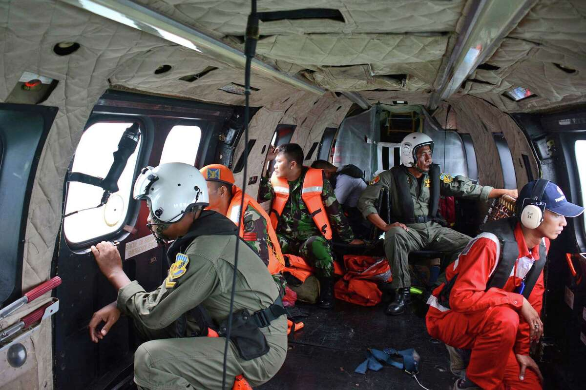 Crew members of an Indonesian Air Force Super Puma helicopter of the 6th Air Squadron look out of the windows during a search operation for the victims of AirAsia Flight 8501 over Java Sea, Indonesia, Thursday, Jan. 1, 2015. The weather improved as the search resumed Thursday for the victims with officials trying to locate the fuselage of the plane that crashed in the sea four days ago.