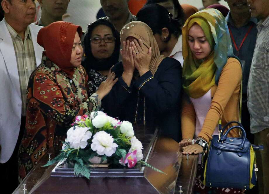 "A relative weeps during the handover of the body of Hayati Lutfiah Hamid, one of the victims of AirAsia Flight 8501, to her family at the police hospital in Surabaya, East Java, Indonesia, Thursday, Jan. 1, 2015. Searchers were racing ""against time and weather"" Thursday to recover the dead from the crash, with a window of good conditions slammed shut by another onslaught of wind and heavy rain. Photo: Dita Alangkara, AP / AP"