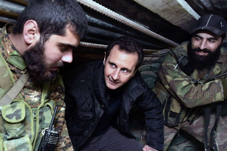 Syrian President Bashar Assad (center) speaks with troops during his visit to the front line in Jobar, Syria. Photo: Associated Press / SANA