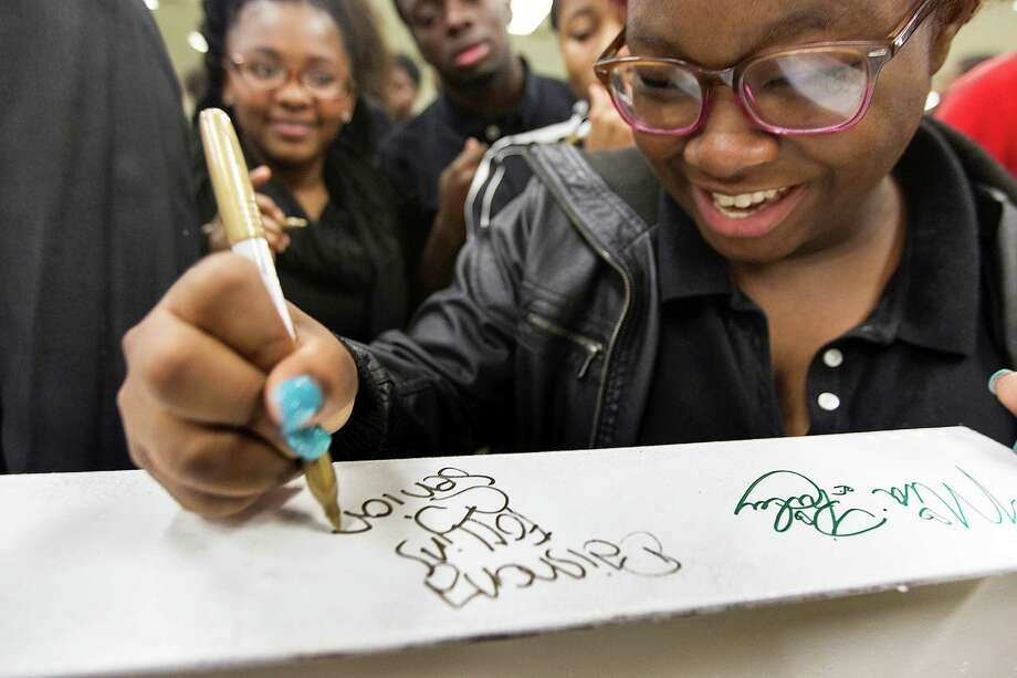 Worthing High School senior Daishona Follins, 17, signs a structural steel I-beam that will be displayed at the new 90,000 square-foot classroom wing that is now under construction after years of delays. Photo: Johnny Hanson, Staff / © 2014  Houston Chronicle