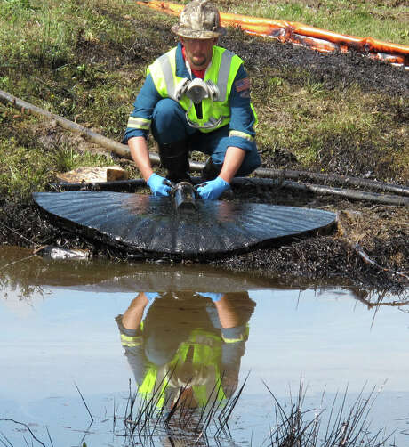 A cleanup worker in March 2013 siphons off oil from the Pegasus pipeline leak near Conway, Ark. Photo: Alan English, MBR / The Log Cabin Democrat