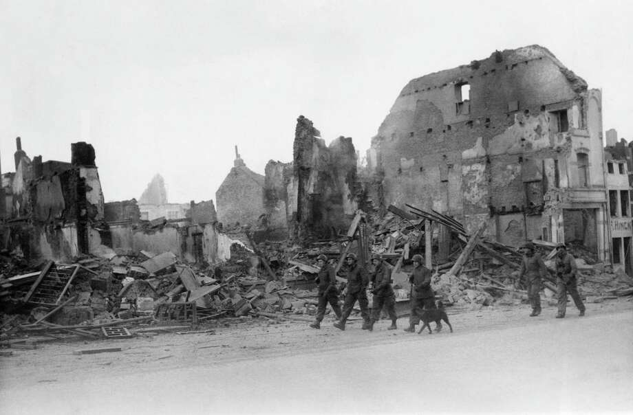 American soldiers walk through a street in war-torn Bastogne, Belgium on Dec. 13, 1945 after the Yanks relieved the divisions trapped there for a week during the German breakthrough in the Belgium-Luxembourg salient in December 1944. Wrecked buildings were caused by shelling and bombing, Bastogne is quiet and peaceful and the stillness is only broken by an occasional transport plane passing overhead or the blows of hammers in repair jobs. (AP Photo/B.H. Rollins ) Photo: B.H. Rollins, ASSOCIATED PRESS / AP1945