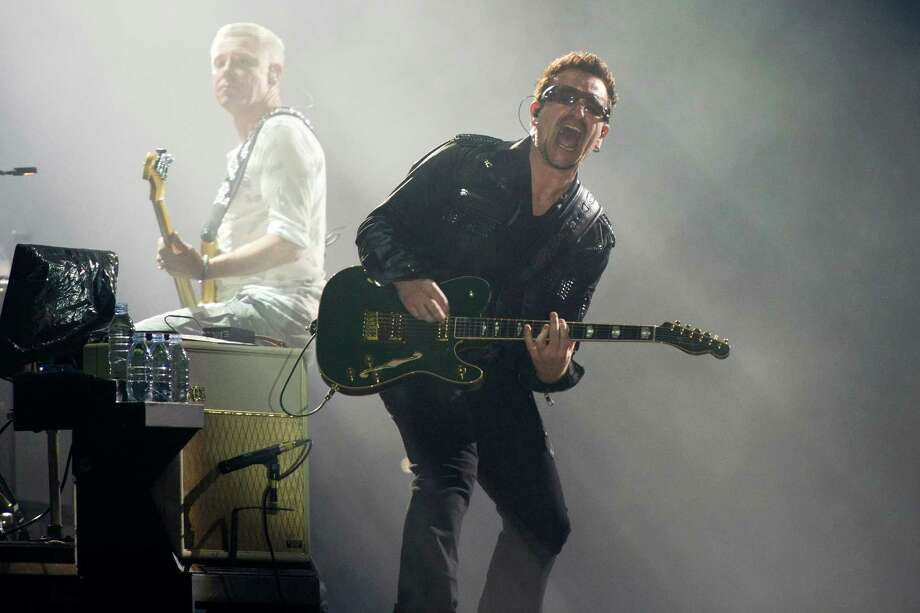 FILE - In this July 20, 2011 file photo, Bono, right, and Adam Clayton, from the rock group U2, perform in concert as part of U2's 360 Tour at the New Meadowlands Stadium in East Rutherford, N.J. Bono wrote on the band's website Thursday Jan. 1, 2015, he may never play guitar again due to injuries suffered in a New York City cycling accident in November. Photo: Charles Sykes, AP / FR170266 AP