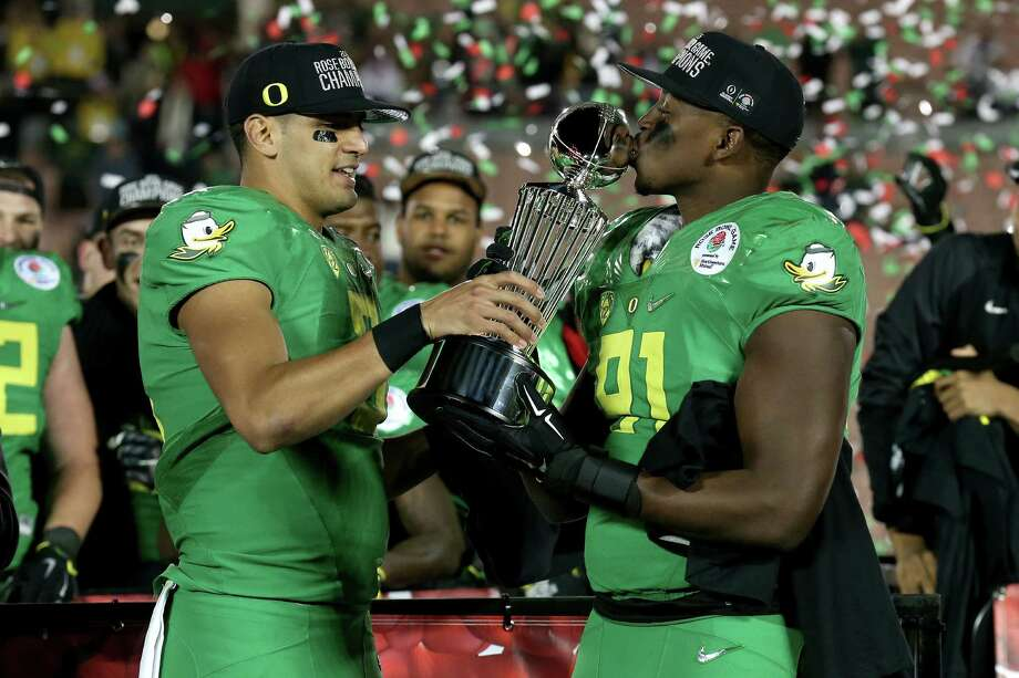 PASADENA, CA - JANUARY 01:  Quarterback Marcus Mariota #8 of the Oregon Ducks hands the Leishman Trophy to linebacker Tony Washington #91 after defeating the Florida State Seminoles 59-20 in the College Football Playoff Semifinal at the Rose Bowl Game presented by Northwestern Mutual at the Rose Bowl on January 1, 2015 in Pasadena, California. Photo: Stephen Dunn, Getty Images / 2015 Getty Images