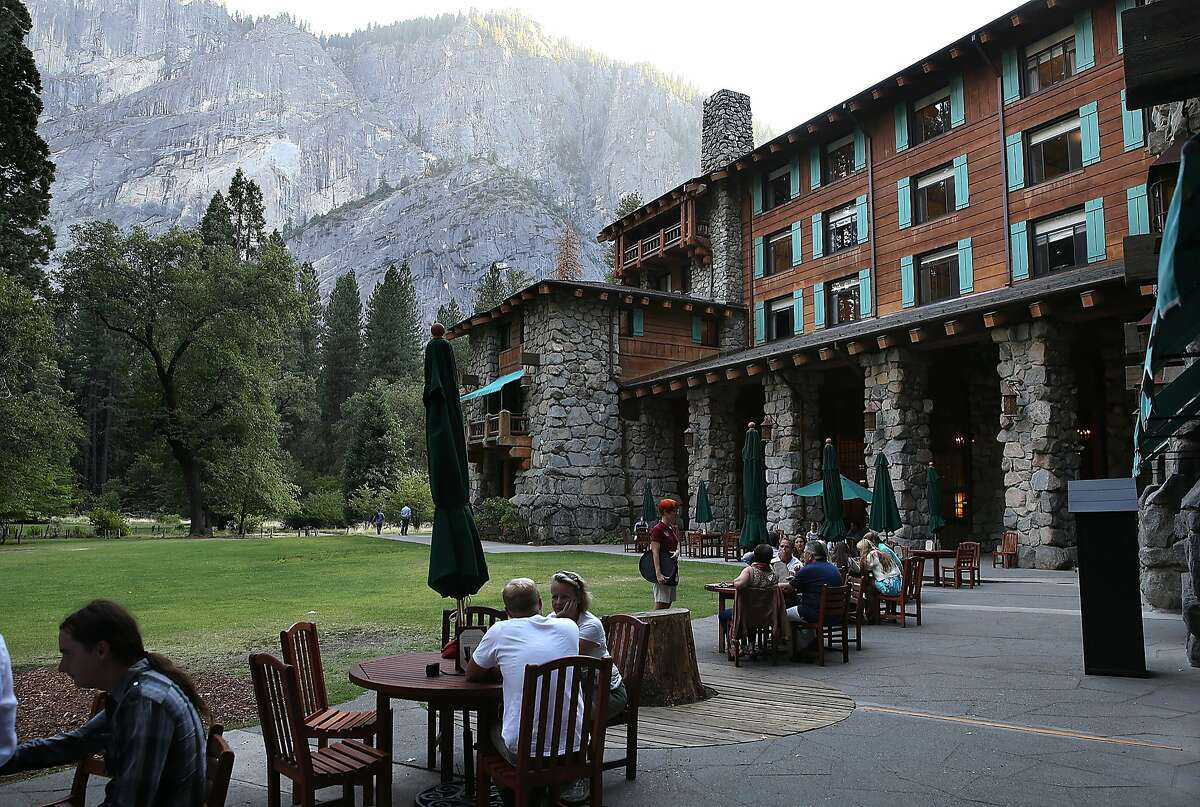 YOSEMITE NTL PARK, CA - AUGUST 28: Park visitors sit outside of the Ahwahnee Hotel on August 28, 2013 in Yosemite National Park, California. As the Rim Fire continues to burn on the western edge of Yosemite National Park, the valley floor of the park remains open. The Rim Fire has charred more than 190,000 acres of forest and is currently 30 percent contained. (Photo by Justin Sullivan/Getty Images)