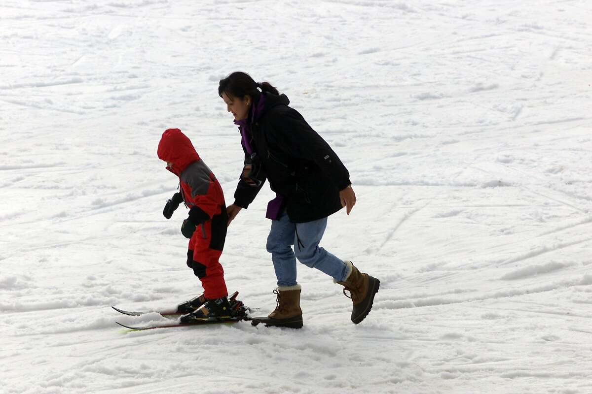 """A woman gives a young child a helping hand as they head towards the """"Turtle"""" run at Yosemite National Park's Badger Pass ski resort on a sunny winter day."""