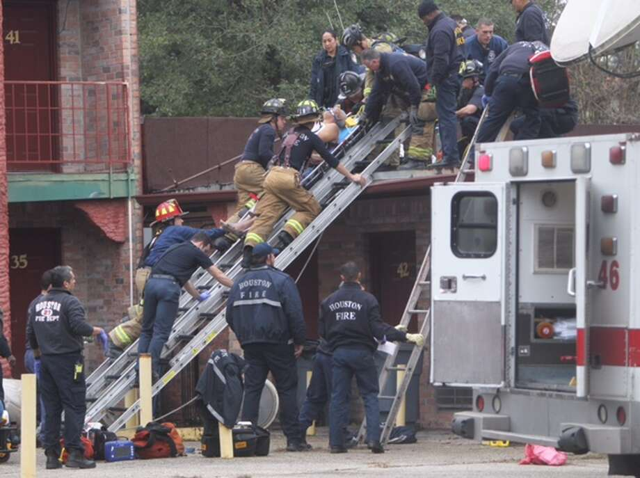 A man was rescued Friday. Jan. 2, 2015 from the roof of  a building after he reportedly had heart attack in south Houston. Photo: Cody Duty | Houston Chronicle