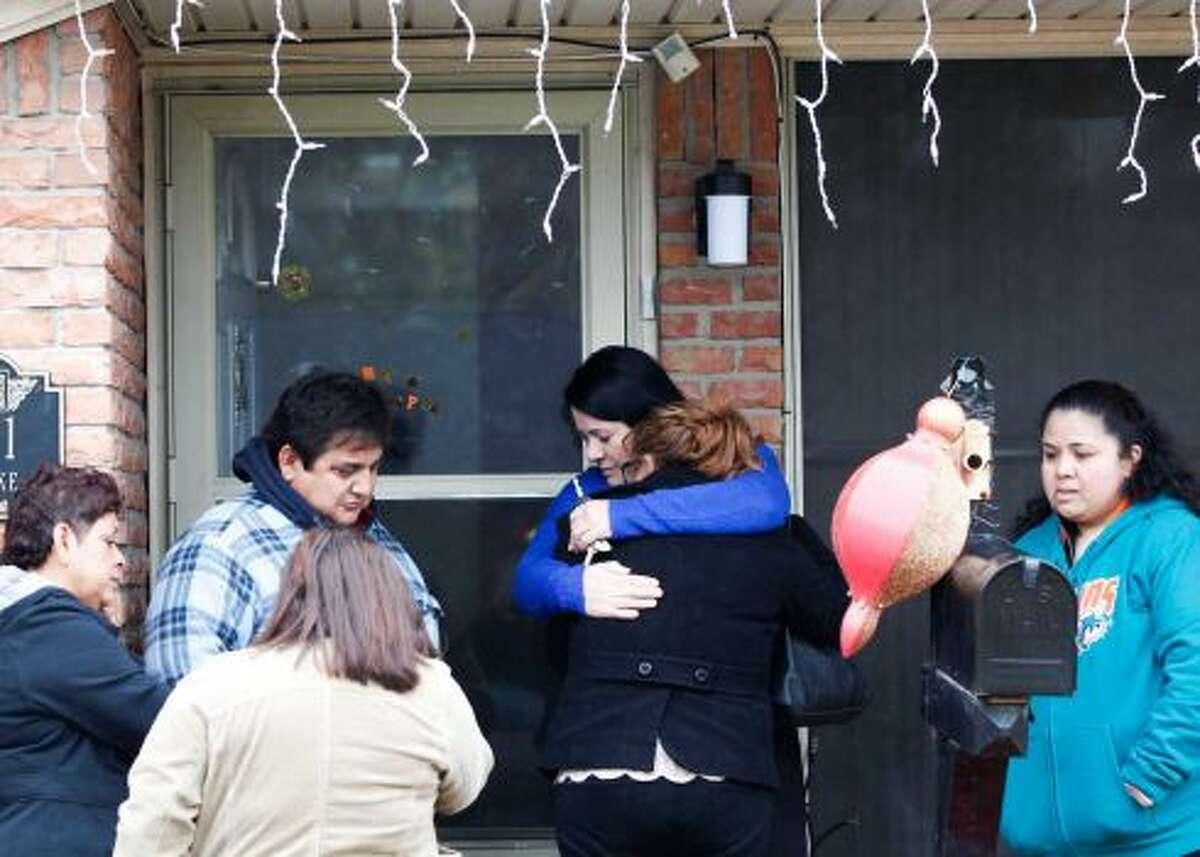 Un amigo de la familia abraza a la hija de Javier Suárez Rivera, Keyla, de 16 años, mientras familiares y amigos lamentan la muerte del hombre debido a una bala perdida en las primeras horas de 2015.
