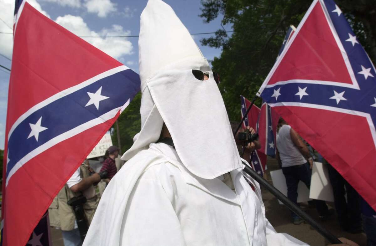 KKK - A Ku Klux Klans member is seen moving to the area assigned to death penalty supporters Thursday June 22, 2000, in Huntsville, Tx. near The Texas Department of Criminal Justice's Huntsville Unit, where convicted murderer Gary Graham is scheduled to be executed at 6 pm. . CONFEDERATE FLAGS.