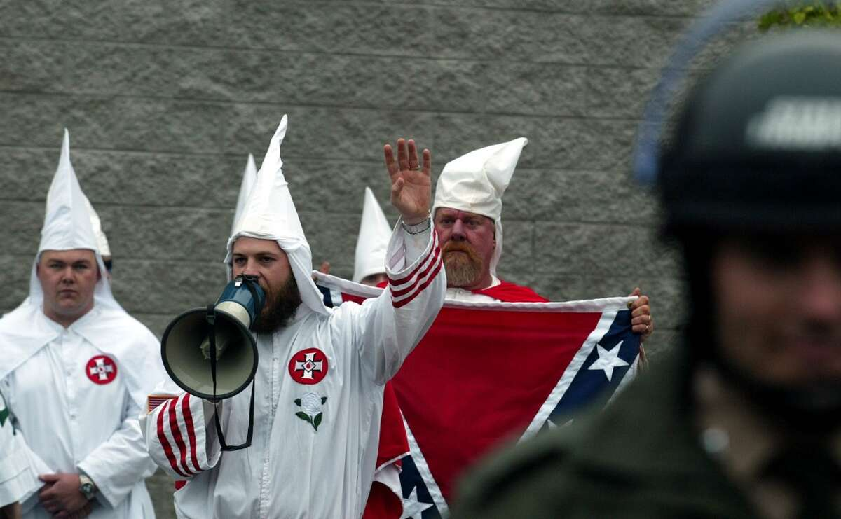 An unidentified Ku Klux Klan member uses a megaphone to speak his message Saturday, March 29, 2003, from behind a line of Tennessee Highway Patrol officers during a rally in Greenville, Tenn. About 30 members of the Ku Klux Klan staged a rare public rally Saturday as 200 counterdemonstrators and more than 100 law enforcement officers looked on. (AP Photo Jason R. Davis)