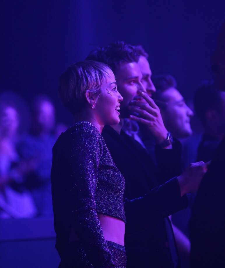 """Singer Miley Cyrus (L) and actor Patrick Schwarzenegger attend the New Year's Eve performance of """"Britney: Piece of Me"""" at Planet Hollywood Resort & Casino on December 31, 2014 in Las Vegas, Nevada. Photo: Gabe Ginsberg, WireImage"""