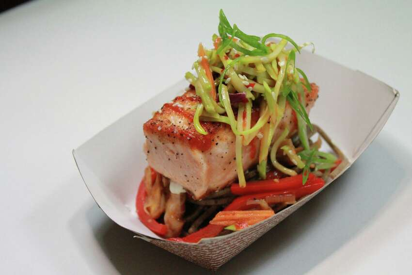 Ginger Soy Salmon: Seared salmon on top of a wheat noodle stir fry and topped with a sweet chile broccoli slaw.