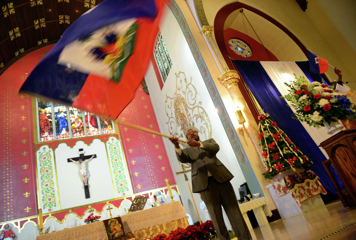 Alexandre Pierre, a member of St. Charles Borromeo Church, waves the Haitian flag during a service celebrating Haiti's independence in Bridgeport, Conn. on Thursday Jan. 1, 2015. Haiti emerged as the first independent black republic in the western hemisphere after defeating Napoleon Bonaparte's army on Jan. 1, 1804.