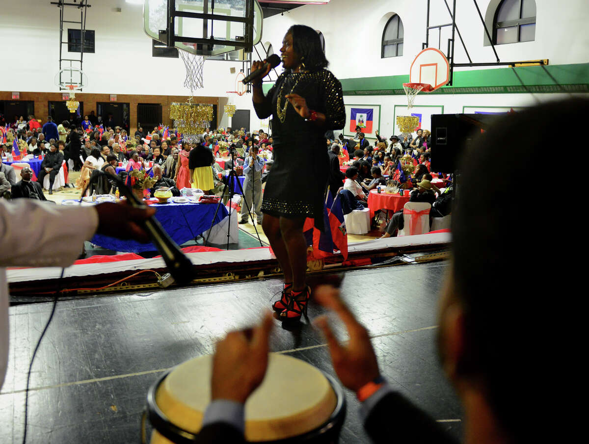 Esther Ervelus sings a traditional Haitian song celebrating Haiti's independence as she is accompanied by Joseph Poteau on drum, during a reception at McGivney Center after a service next door at St. Charles Borromeo Church in Bridgeport, Conn. on Thursday Jan. 1, 2015. Haiti emerged as the first independent black republic in the western hemisphere after defeating Napoleon Bonaparte's army on Jan. 1, 1804.