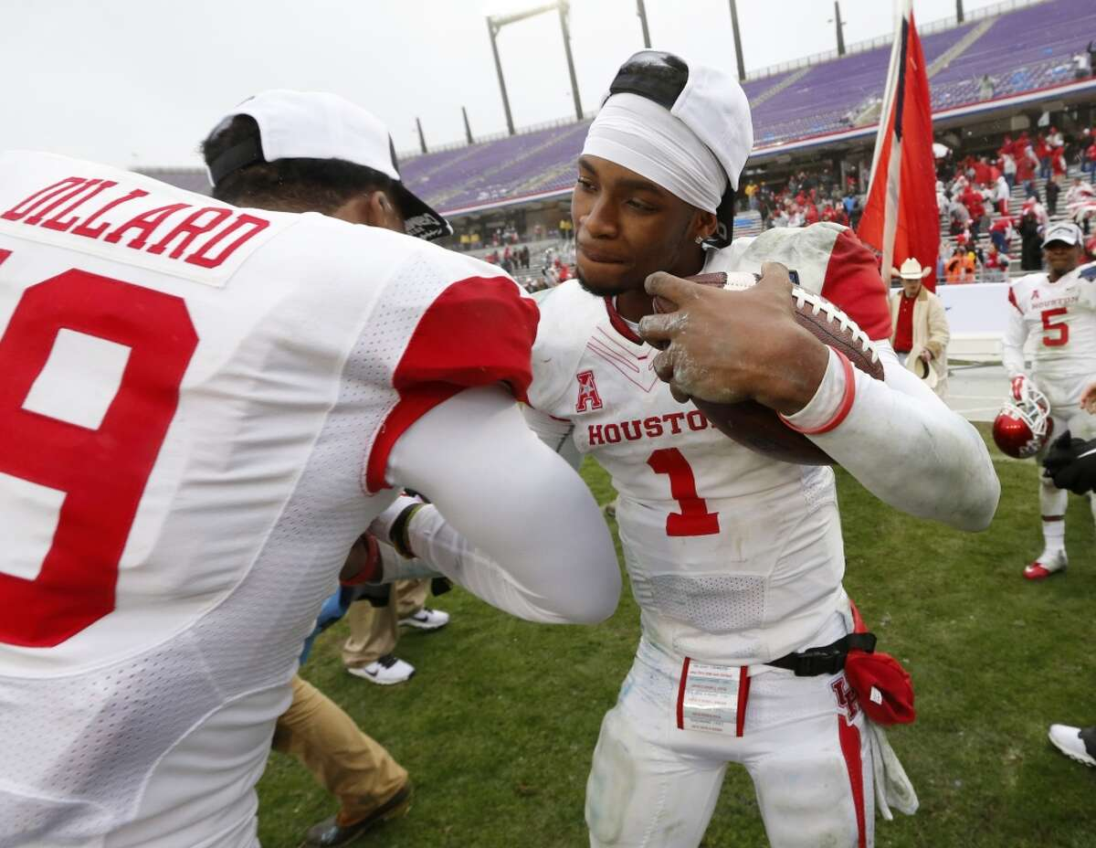 Houston defensive back Marcus Dillard (19) congratulates quarterback Greg Ward Jr. (1) after they defeated Pittsburgh 35-34 in the Armed Forces Bowl.