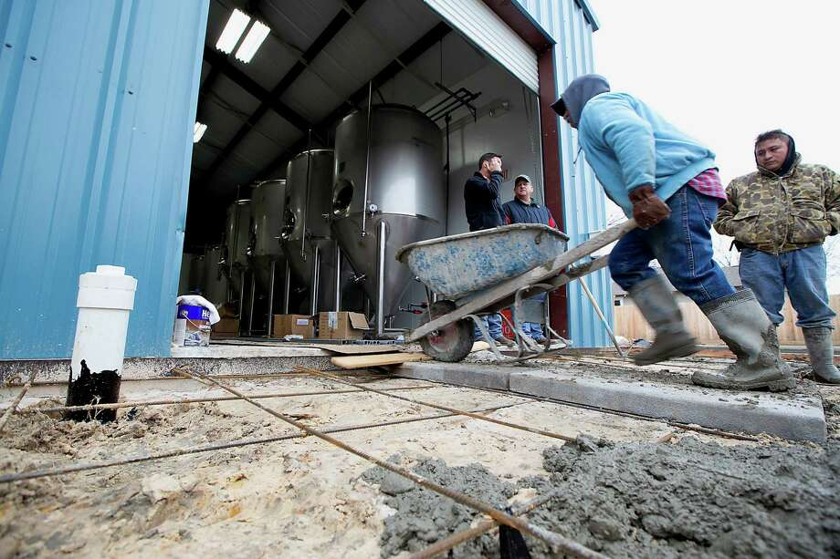 A worker with Piper Whitney Construction moves a wheel barrow of concrete during a concrete pour Wednesday at the Town in City Brewing Company on West Cavalcade. Photo: James Nielsen, Staff / © 2014  Houston Chronicle