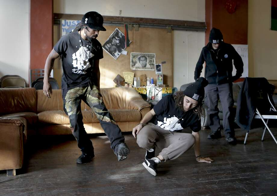 """Khafre James the executive director and founder of """"Hip Hop For Change"""" demonstrates a few break dancing moves to  Jada Carter, 16 a former student of the hip hop course taught by James' organization, at their offices in Oakland, Calif., as seen on Wednesday Dec. 31, 2014. Malik Diamond,  a team member of Hip Hop For Change is seen at right. Photo: Michael Macor, The Chronicle"""