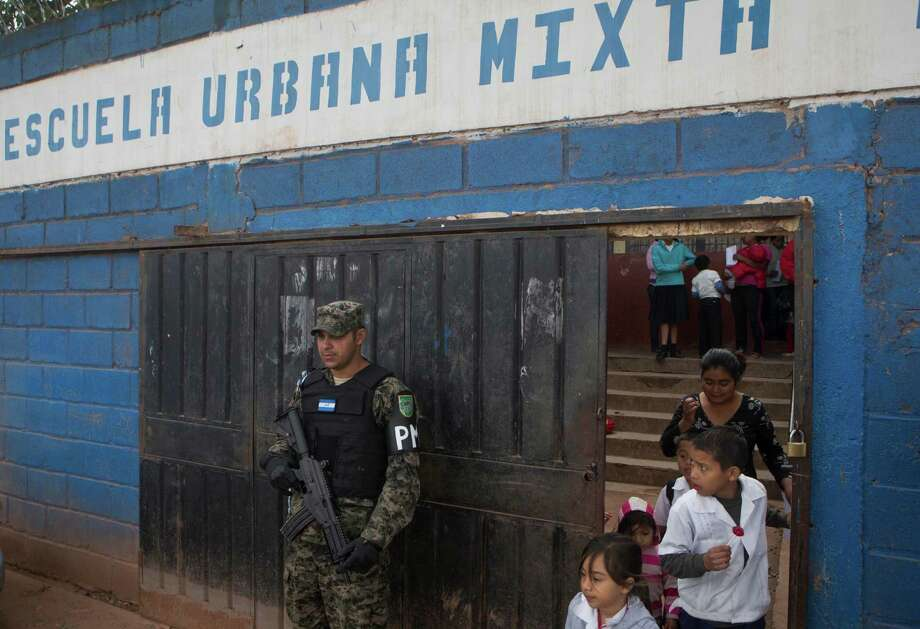 In this photo Nov. 28, 2014 photo, a member of Hondura's Military Police, stands guard at the entrance of a school, during the last day of class, in the Canaan neighborhood of Tegucigalpa, Honduras. Street gangs control most schools in Tegucigalpa, where a lot of the students are gangsters, along with their parents. (AP Photo/Esteban Felix) Photo: Esteban Felix, STF / AP