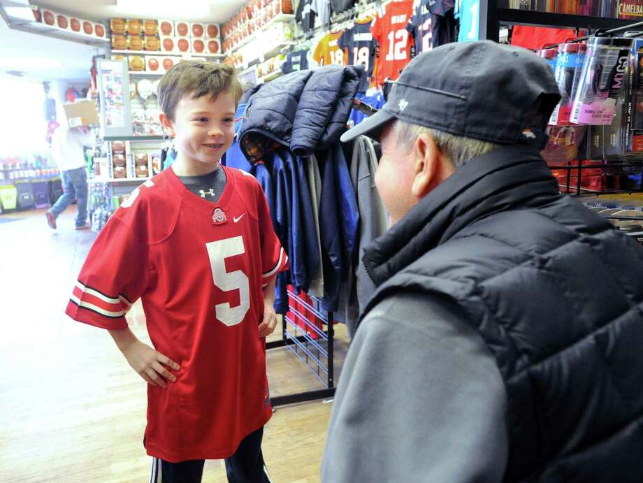 At left, John Riehl, 10, tries on a Ohio State University football jersey as his father, John Riehl of Greenwich, at right, looks on inside the Bruce Park Sports store in Greenwich, Conn., Friday, Jan. 2, 2015. The younger Riehl said he likes Ohio State but the University of Notre Dame is his favorite college football team. The College Football Playoff National Championship title game will take place Monday night, January 12, at 8:30 p.m. in Arlington, Texas, and features the University of Oregon against Ohio State University. The game is being televised on ESPN. Photo: Bob Luckey / Greenwich Time