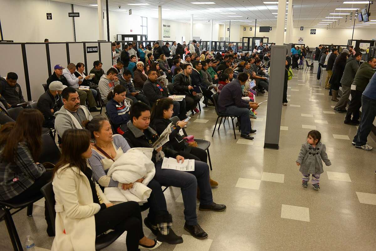 Scores of people wait for their turn at the DMV on Friday, January 2, 2014 in San Jose, Calif. The DMV is allowing undocumented immigrants to obtain driver's licenses under AB 60.