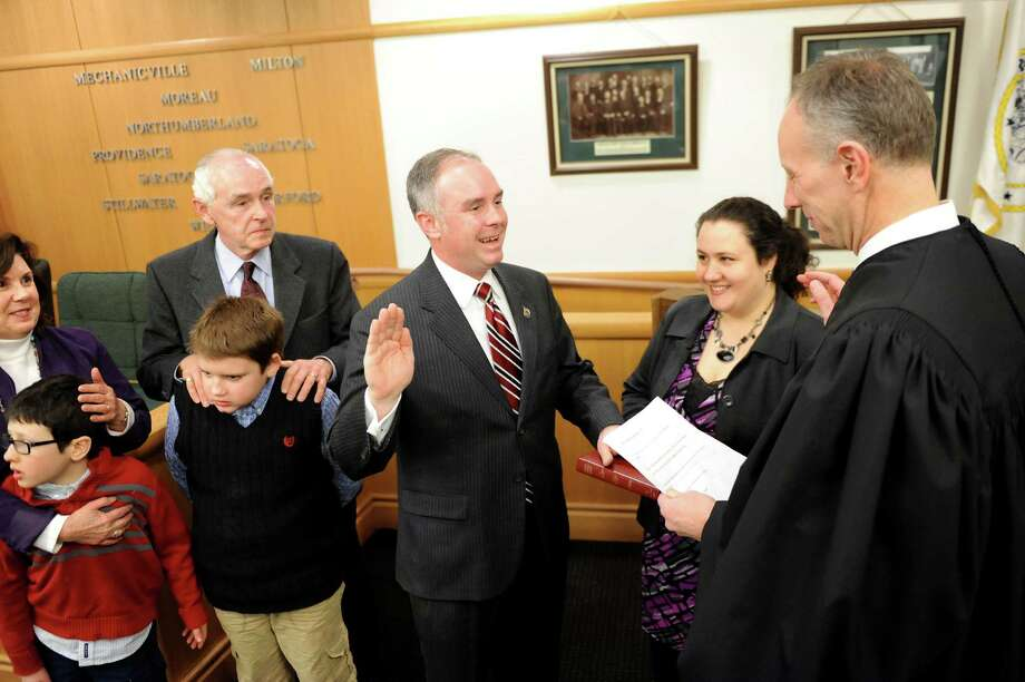 Matthew Veitch, center, is sworn as the Chairman of the Board by Judge James A. Murphy III, right, on Friday, Jan. 2, 2015, at the Saratoga County Board of Supervisors in Ballston Spa, N.Y. Joining him are his parents Michael and Gail Veitch, his sons David Veitch, 10, left, and Jacob Veitch, 12, and his wife Stephanie holds the Bible. (Cindy Schultz / Times Union) Photo: Cindy Schultz / 00030040A