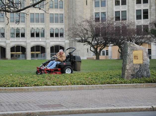 A man mowing the lawn in front of the SUNY System Administration Building on Broadway is not a usual sight in January on Friday, Jan. 2, 2015 in Albany, N.Y.  (Lori Van Buren / Times Union) Photo: Lori Van Buren