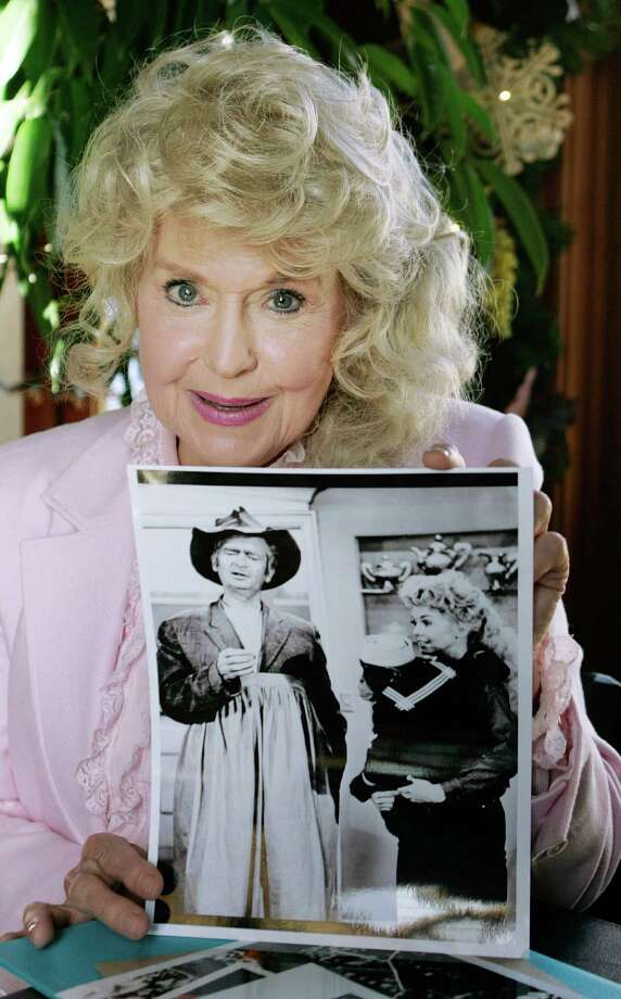 """FILE - In this Jan. 8, 2009 file photo, Donna Douglas, who starred in the television series """"The Beverly Hillbillies"""" holds a publicity picture of herself from the show, in Baton Rouge, La. Douglas, who played the buxom tomboy Elly May Clampett on the hit 1960s sitcom has died. Douglas, who was 82, died Thursday, Jan. 1, 2015, in Baton Rouge, where she lived, her niece, Charlene Smith, said. (AP Photo/Bill Haber, File) ORG XMIT: CAET272 Photo: Bill Haber / AP"""