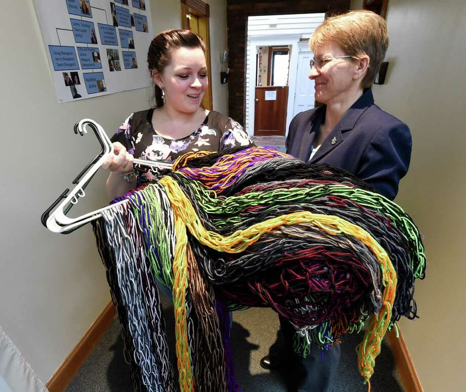 Katie Drobner, 22, of Selkirk, left, who started Katie's Koats three years ago presented Liz Hitt, executive director of the Homesless and Travelers Aid Society(HATAS) with 36 scarves that she made for the coat drive this year at a press conference held Friday Jan. 2, 2015, in Albany, N.Y.,  announcing the large number of coats received this year.      (Skip Dickstein/Times Union) Photo: SKIP DICKSTEIN / 00030035A