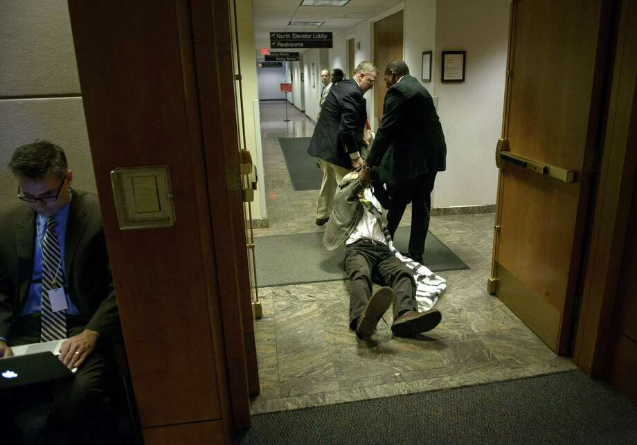 A protester is dragged from a hearing in December at the Federal Communications Commission. The protesters were urging net neutrality, the concept that all online traffic should be given the same access to networks. Photo: BRENDAN SMIALOWSKI, Staff / 2014 Brendan Smialowski