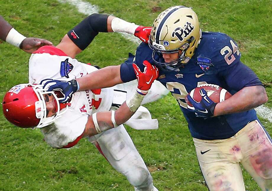 Houston Cougars defensive back Adrian McDonald (16, left) is stiff armed by Pittsburgh Panthers running back James Conner (24) in the fourth quarter of the Armed Forces Bowl. The Cougars defeated the Pittsburgh Panthers 35-34 in the Armed Forces Bowl at Amon G. Carter Stadium Friday January 2, 2015 in Fort Worth, Texas. Photo: Ron Jenkins, Star-Telegram