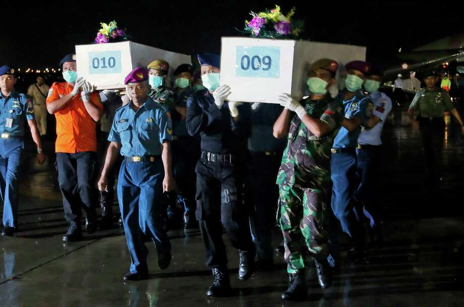 Indonesian military personnel carry coffins containing the bodies of  victims of AirAsia Flight 8501 upon arrival at Juanda Naval Airbase in Surabaya, East Java, Indonesia, Friday, Jan. 2, 2015. After nearly a week of searching for the victims of AirAsia Flight 8501, rescue teams battling monsoon rains had their most successful day yet on Friday, more than tripling the number of bodies pulled from the Java Sea, some still strapped to their seats. (AP Photo/Dita Alangkara) ORG XMIT: DA117 Photo: Dita Alangkara / AP