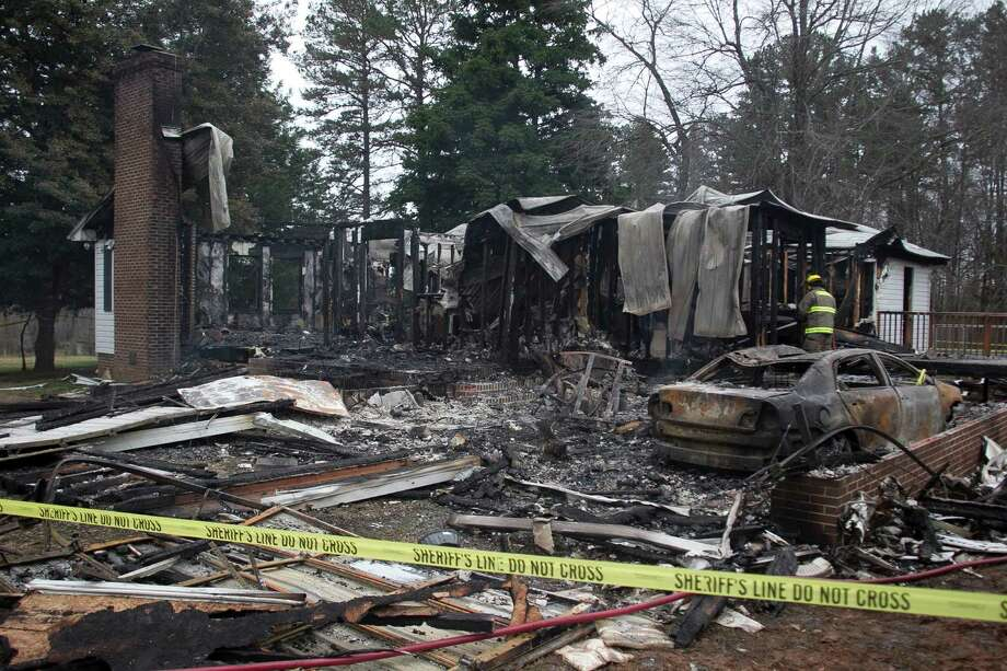 A firefighter works at the home of Jerome Faulkner, 73, and his wife Dora, 62, on Friday near Oxford, N.C. Their bodies were found in their stolen SUV being driven by Eric Campbell of Alvin, police said. Photo: Robert Willett / 2014, The News & Observer