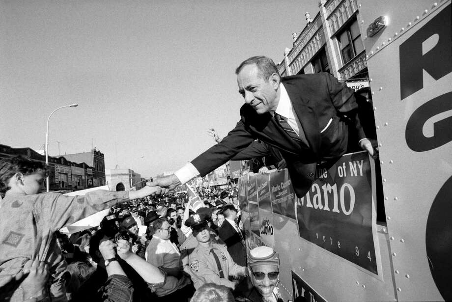 FILE -- From a campaign bus, Gov. Mario Cuomo of New York shakes hands with supporters, Oct. 30, 1994. Cuomo, a three-term governor who commanded the attention of the country with a compelling public presence and a forceful defense of liberalism, died at home in Manhattan on Jan. 1, 2015. He was 82. (James Estrin/The New York Times) ORG XMIT: XNYT137 Photo: JAMES ESTRIN / NYTNS
