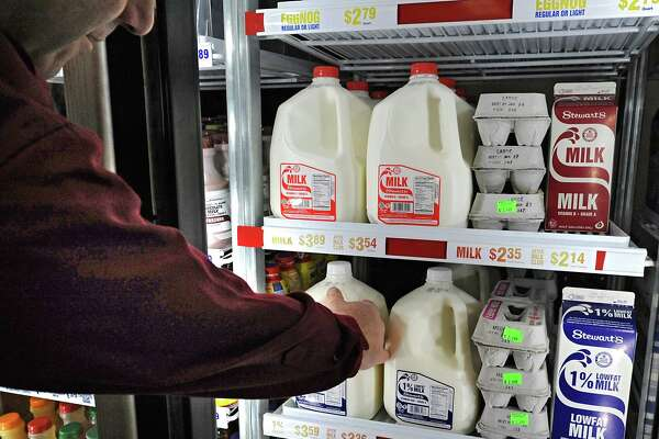 A customer reaches for a gallon of 1% milk at a Stewart's Shops on Friday, Jan. 2, 2015 in Latham, N.Y. Stewart's Shops will be lowering their milk prices 30 cents Monday. (Lori Van Buren / Times Union)